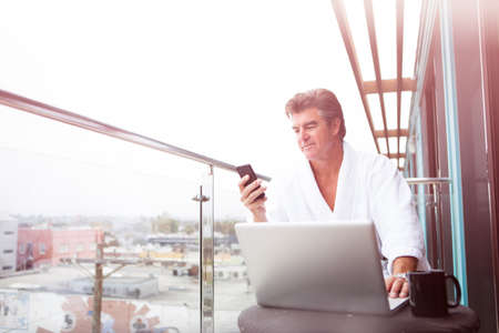 Attractive Man enjoying his morning coffee on his computer outside his hotel room