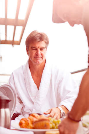 hospitality staff: Attractive Man being served Breakfast outdoors on his hotel balcony