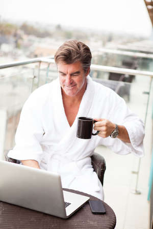 hotel balcony: Attractive Man enjoying his morning coffee on his computer outside his hotel room