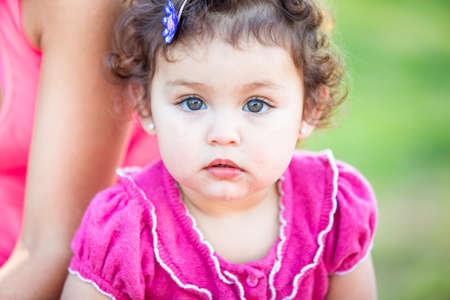Cute Toddler girl in pink looking at camera Фото со стока