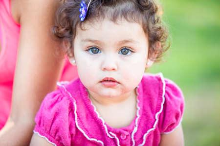 Cute Toddler girl in pink looking at camera Stock fotó