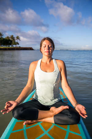 Pretty woman in meditation after her SUP Yoga on the water