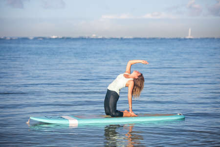Pretty woman in back bend doing SUP Yoga on the water 版權商用圖片