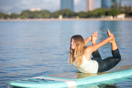 Pretty woman in bow pose doing SUP Yoga on the water