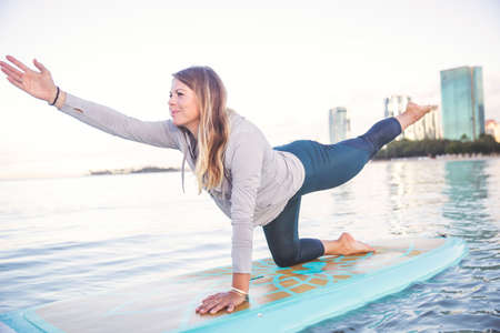Pretty woman in modified warrior doing SUP Yoga on the water