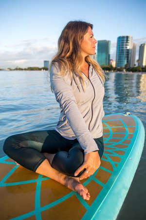 Pretty woman in side twist doing SUP Yoga on the water