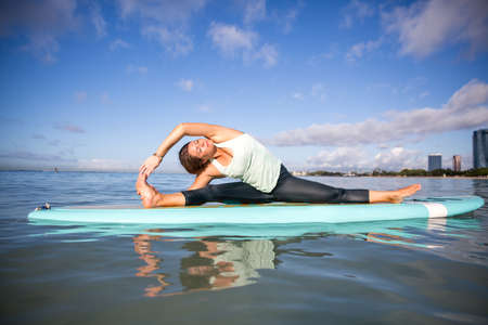 Pretty woman in side bend doing SUP Yoga on the water