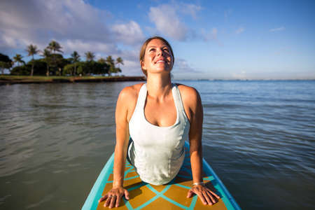 Pretty woman in cobra position doing SUP Yoga on the water