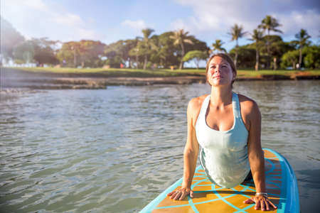 Sunny morning work out a pretty young woman in SUP Yoga practice cobra pose in Ala Moana Hawaii