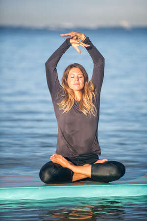 Sunny morning work out a pretty young woman in SUP Yoga practice  Ala Moana Hawaii