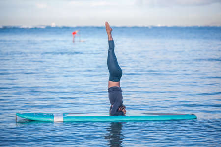 Sunny morning work out a pretty young woman in SUP Yoga practice head stand at Ala Moana Hawaii