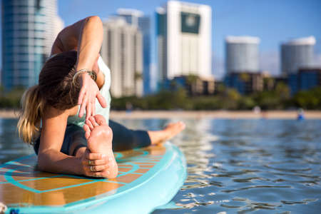 Sunny morning work out a pretty young woman in SUP Yoga practice side bend leg stretch in Ala Moana Hawaii Stockfoto