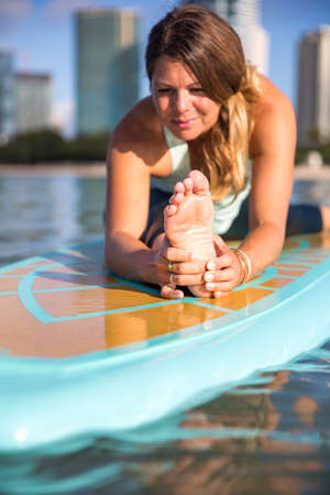 Sunny morning work out a pretty young woman in SUP Yoga practice leg stretch in Ala Moana Hawaii