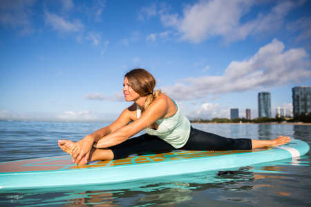 Sunny morning work out a pretty young woman in SUP Yoga practice side stretch Pose in Ala Moana Hawaii