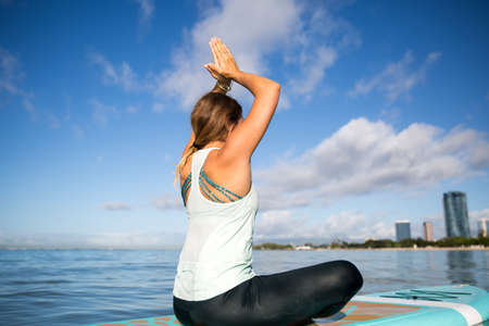 Sunny morning work out a pretty young woman in SUP Yoga practice cross leged prayer Pose in Ala Moana Hawaii