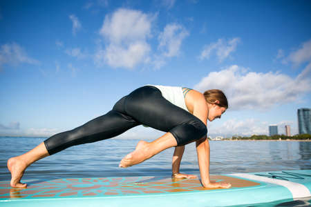 Sunny morning work out a pretty young woman in SUP Yoga practice in Ala Moana Hawaii