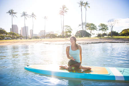 Sunny morning sun flare moment of a pretty young woman in SUP Yoga practice in twist pose