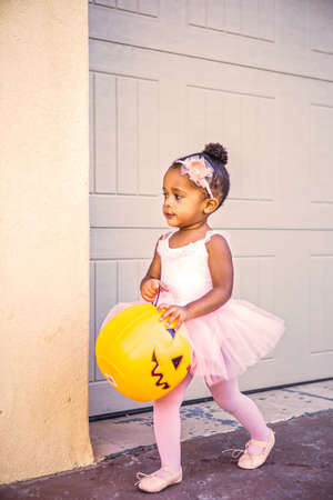 Cute 2 year old girl trick or treating in her ballet outfit