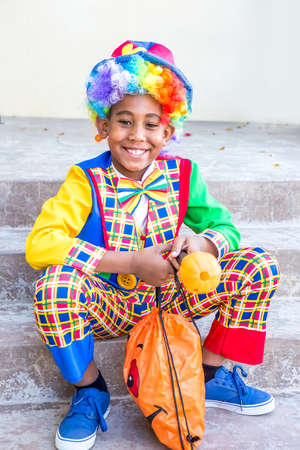 Preteen boy in a colorful costume ready to trick or treat looking in his candy bag 版權商用圖片