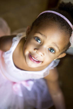 Pretty toddler girl looking up at camera with beautiful blue gray eyes