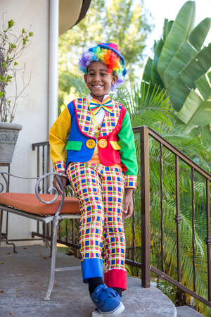 Smiling preteen boy in a colorful costume ready to trick or treat