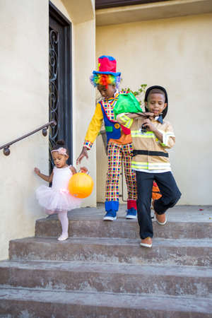 Siblings in costume at a home to trick or treat 版權商用圖片