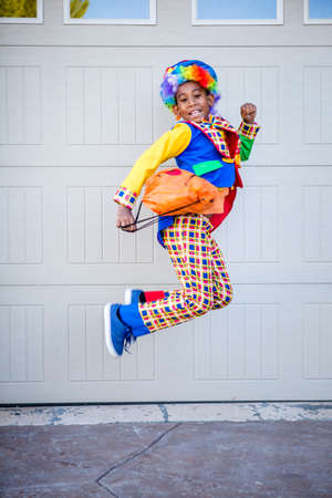 Jumping preteen boy in a colorful costume excited about Halloween 版權商用圖片