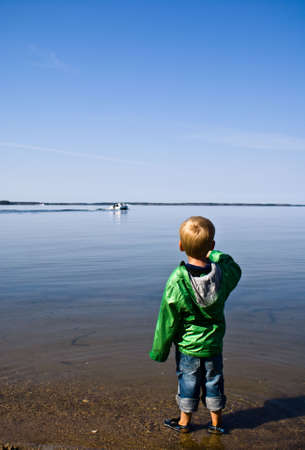 A small child looking out over a lake at a disappearing speedboat
