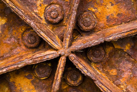 A close-up of a rusty tractor wheel showing the effects of exposure on metal