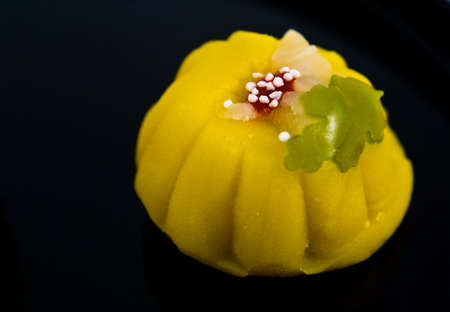 A single Japanese sweet (wagashi) shot close-up on a black lacquer plate