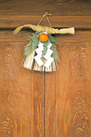 A traditional Japanese doorway displaying a New Years wreath