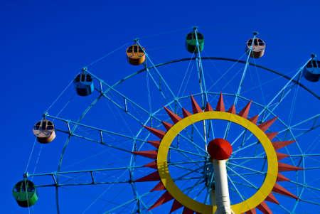 A colorful ferris wheel shot against a blue sky, left view Stock Photo