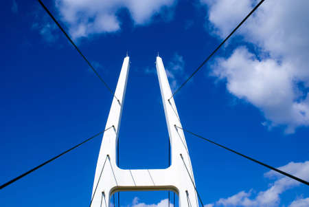A white suspension bridge against a blue sky with clouds Stock Photo