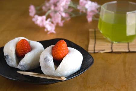 Two Japanese sweets (Ichigo Daifuku) with green tea and flowers