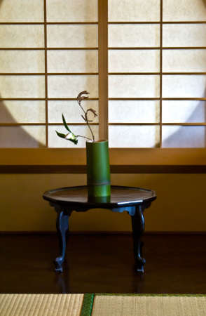 niche: A white rose in a bamboo vase against a Japanese paper screen window