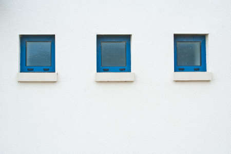 Three small windows with blue frames on a white wall