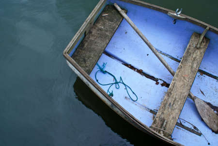 A portion of an aged rowboat on the water taken from above photo