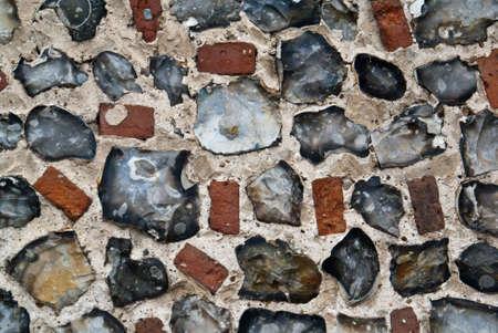 An exterior flint stone and brick wall