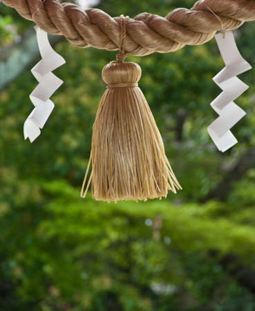 A rope and folded paper outside a shrine in Japan Stock Photo