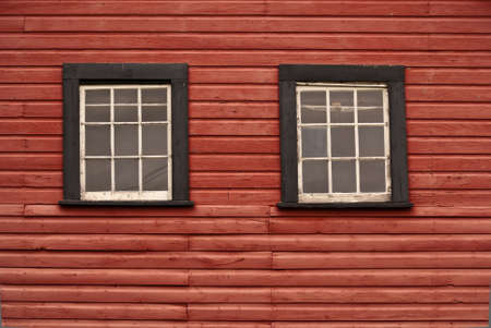 Two black and white windows on a red painted wood prairie building