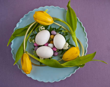 An Easter table centerpiece of colourful eggs, tulips and flowers on a blue plate Stock Photo - 7912182