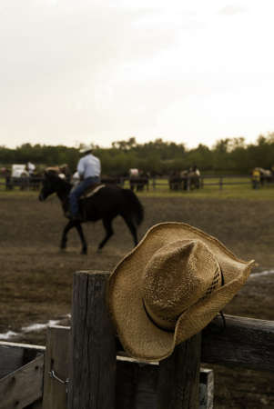 A cowboy hat hung over the fence at an agricultural fair with a horse and rider in the background