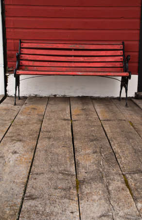 A bench of red painted wood and black iron stands behind an aged wooden floor and painted red exterior wall at an old railway station Stock Photo