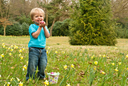 A toddler smiles while proudly holding an Easter egg Stock Photo