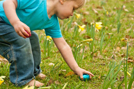 A closeup of a toddler picking up Easter eggs on an Easter egg hunt
