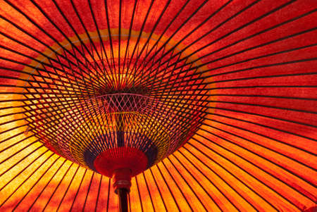 A closeup of a red, Japanese parasol from below with sun shining down Stok Fotoğraf