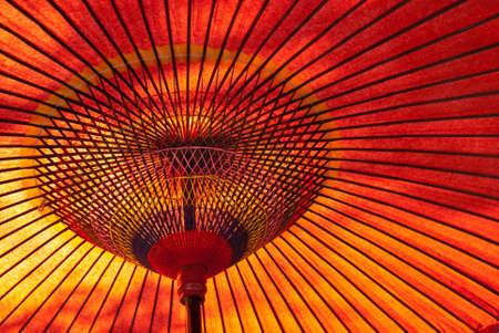 Een close-up van een rood, Japanse parasol van onderen met zon schijnt neer