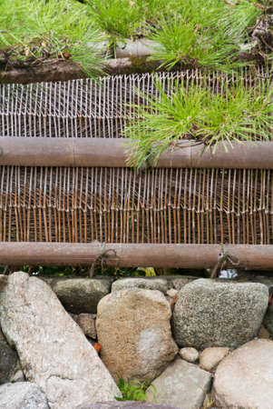 A Japanese stone wall with bamboo fence and overhanging pine tree Stock Photo