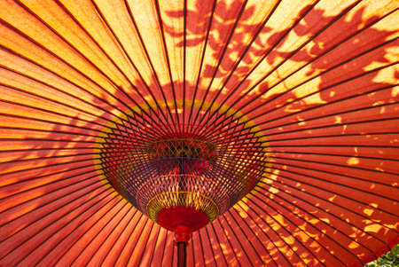 A closeup of a red, Japanese parasol from below with sun shining down Stock Photo