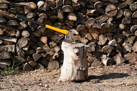 A yellow axe used for chopping firewood with blade in  chopping block2